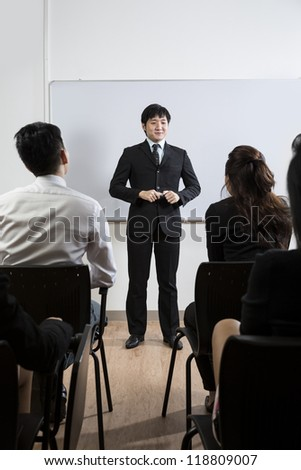 Happy looking Chinese Business man giving presentation