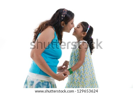 happy looking indian mother and daughter kissing - stock photo