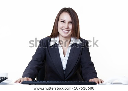 happy looking young looking business woman sitting at her desk - stock photo