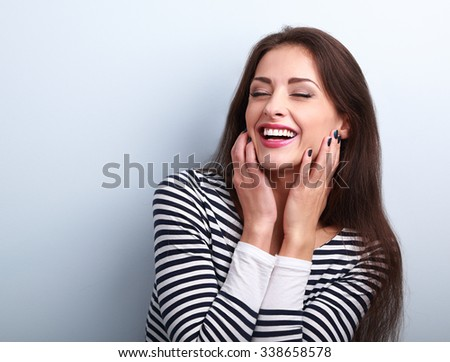 Happy loudly laughing woman holding hands the face on blue background - stock photo