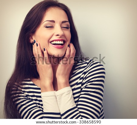 Happy loudly laughing woman holding hands the face. Vintage closeup toned portrait - stock photo