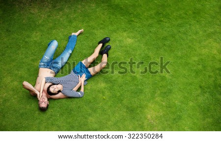 Happy Love Young couple lying on green grass together outdoor - stock photo