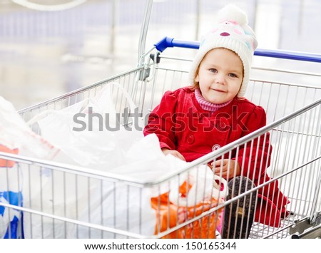 happy lovely baby sitting in shopping trolley - stock photo