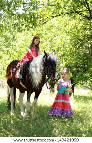 Happy lovely children ride on a horse and smiling in a summer park
