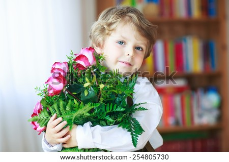 Happy lovely smiling little kid boy with blooming pink roses in bunch, congratulating his mum for mothers day or dad for fathers day - stock photo
