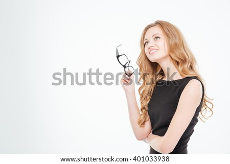 Happy lovely young businesswoman holding glasses and thinking over white background  - stock photo