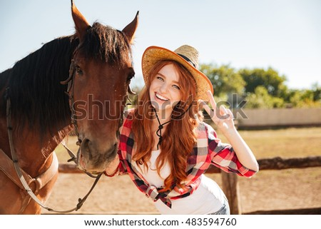 Happy lovely young woman cowgirl standing with horse and showing peace sign
