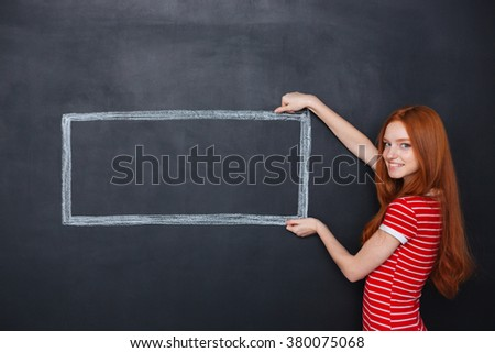 Happy lovely young woman with long red hair holding drawn frame over chalkboard background - stock photo