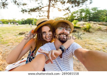 Happy lovers, attractive woman and man walking in park  enjoying romance.   funny couple making selfie, smiling and have fun together. - stock photo
