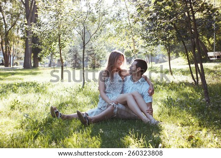 Happy lovers in Park. Emotional portrait of couple on grass in morning. Girl on arms of guy. Romantic photo
