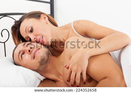 Happy lovers kissing and playing in bed at home - stock photo