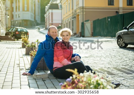 happy lovers sitting together in the street