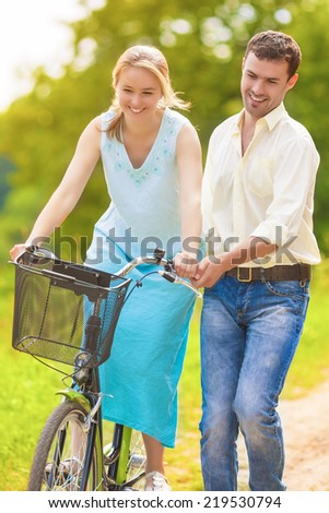 Happy Loving Caucasian Couple Having Fun Together Riding Bike Outdoors. Vertical Image