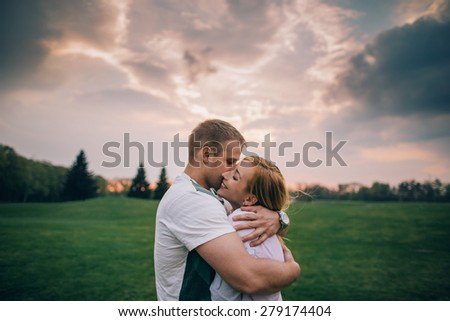 Happy loving couple. Beautiful young couple bonding to each other against cloudy sunset - stock photo