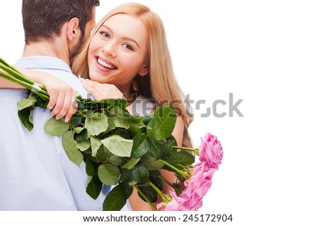 Happy loving couple. Beautiful young loving couple hugging while woman holding bouquet of pink roses and smiling and both standing isolated on white background   - stock photo