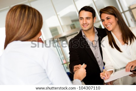 Happy loving couple checking in at a hotel - stock photo