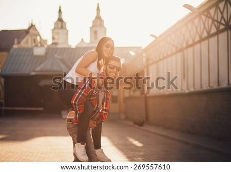 Happy loving couple. funny young man piggybacking his girlfriend. sunset - stock photo