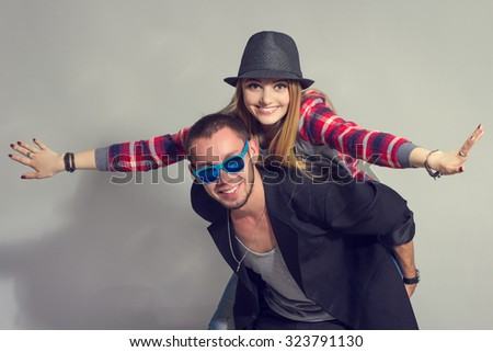 Happy loving couple. Happy young man piggybacking his girlfriend while keeping arms outstretched - stock photo