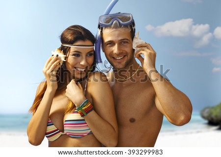 Happy loving couple hugging on the beach, listening to murmur of sea in seashell, smiling.
