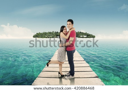 Happy loving couple hugging together and standing on a pier at tropical beach - stock photo