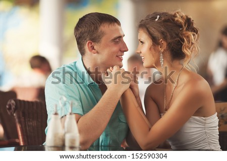 Happy loving Couple in Cafe, man and woman at romantic dating. Man and woman talking in a cafe restaurant. young men whispers to his girlfriend, couple in love. Hugging couple. man and woman in love - stock photo