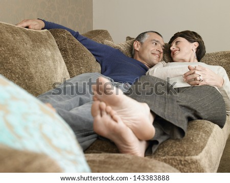 Happy loving couple lying together on sofa