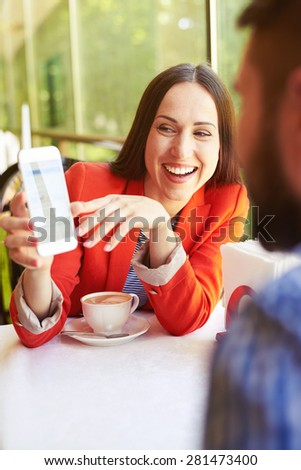 happy loving couple on a date at the restaurant. young beautiful woman laughing and showing her cellphone to man - stock photo