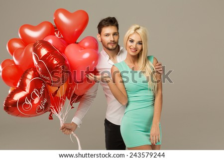 Happy loving couple on grey background with heart balloons - stock photo