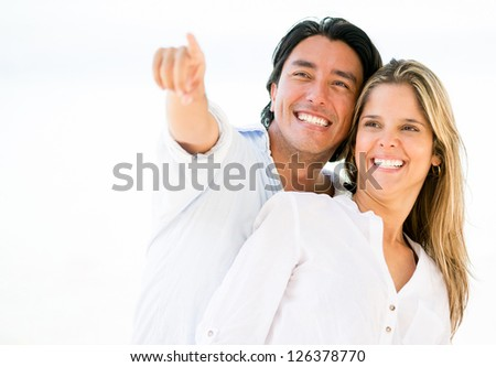 Happy loving couple outdoors pointing away - stock photo