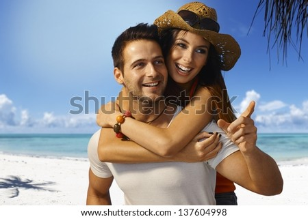 Happy loving couple piggyback on tropical beach at summertime, smiling, looking away. - stock photo