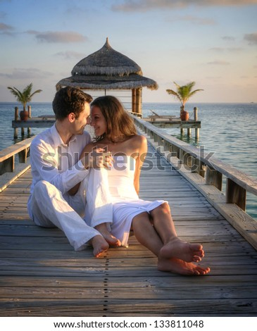 Happy loving couple posing in white clothes on a pier