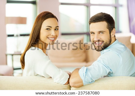 Happy loving couple. Rear view of beautiful young loving couple sitting together on the couch and smiling - stock photo
