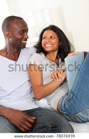 Happy loving couple sitting in sofa with electronic tablet - stock photo