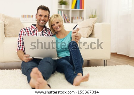Happy loving couple sitting on the floor and using laptop and showing credit card - stock photo
