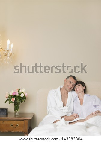 Happy loving couple sitting together in bed