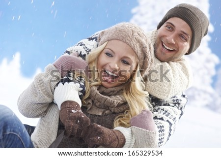 Happy loving couple sledging at wintertime outdoors, laughing. - stock photo