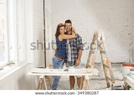 Happy loving couple smiling and embracing in home under renovation, looking at camera.