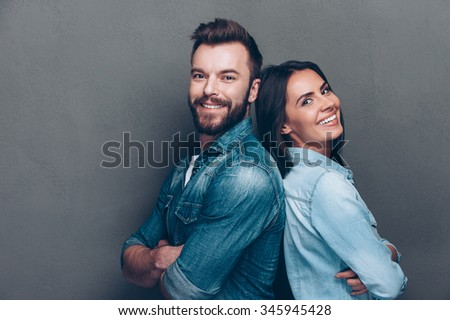 Happy loving couple. Studio shot of beautiful young couple in jeans wear standing back to back and smiling  - stock photo