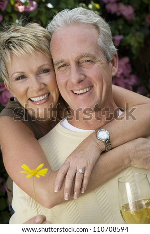 Happy loving couple with flower and wine glass - stock photo