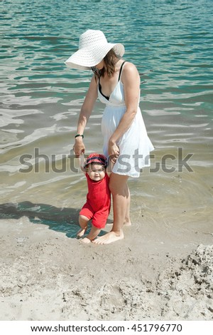 Happy loving family during summer vacation on white beach Mother in the hat and daughter. happy mother holding baby smiling on beach in sunlight. outdoor shot.