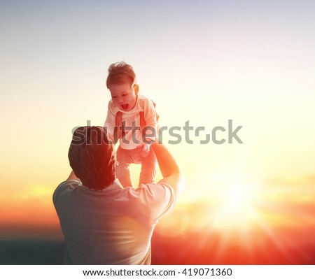 Happy loving family. Father and his daughter baby girl playing and hugging outdoors. Concept of Father's day. - stock photo