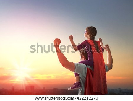 Happy loving family. Father and his daughter child girl playing outdoors. Daddy and his child girl in an Superhero's costumes. Concept of Father's day. - stock photo