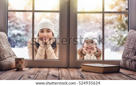 Happy loving family! Mother and child girl having fun, playing and laughing on snowy winter walk in nature. Frost winter season. Child and mom looking in windows, standing outdoors. View indoors home.