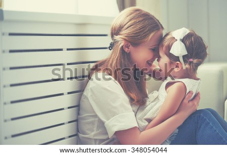 Happy loving family. mother and child girl playing, kissing and hugging - stock photo