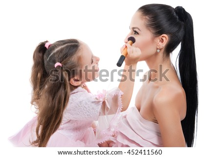 Happy loving family. Mother and daughter are doing your makeup and having fun. Mother and daughter laughing painting each other