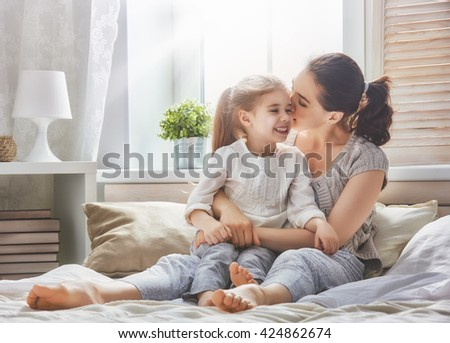 Happy loving family. Mother and her daughter child girl playing and hugging. - stock photo