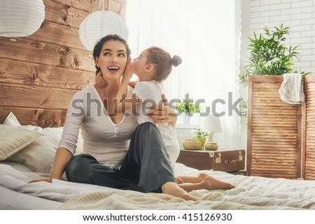 Happy loving family. Mother and her daughter child girl playing and hugging. Daughter whispering to mom a secret. - stock photo