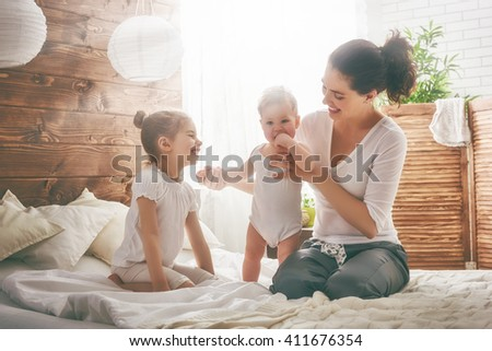 Happy loving family. Mother and her daughters children girls playing and hugging. - stock photo