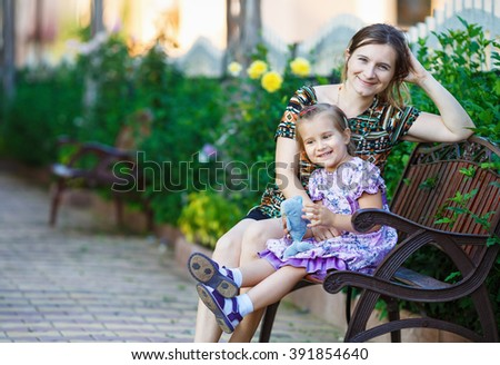 Happy loving family. Mother and little daughter sit on a park bench on a background of bright green foliage. - stock photo