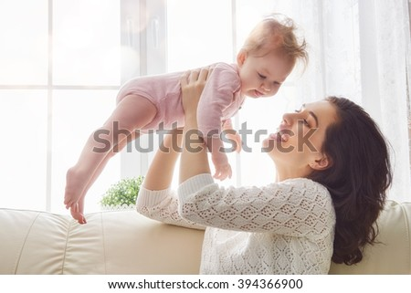 happy loving family. mother playing with her baby in the bedroom. - stock photo